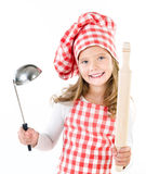 Smiling cute little girl in chef hat with ladle and  rolling pin. Isolated on a white Royalty Free Stock Photos