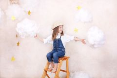 A smiling cute little girl flies in the sky with clouds and stars. Little astrologer Little traveler. The concept of preschool edu. Cation of the child. Close-up stock images