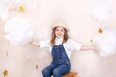 A smiling cute little girl flies in the sky with clouds and stars. Little astrologer Little traveler. The concept of preschool edu. Cation of the child. Close-up royalty free stock images
