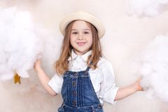 A smiling cute little girl flies in the sky with clouds and stars. Little astrologer Little traveler. The concept of preschool edu. Cation of the child. Close-up stock photo