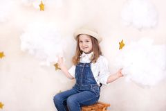 A smiling cute little girl flies in the sky with clouds and stars. Little astrologer Little traveler. The concept of preschool edu stock photo
