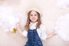 A smiling cute little girl flies in the sky with clouds and stars. Little astrologer Little traveler. The concept of preschool edu. Cation of the child. Close-up royalty free stock photo