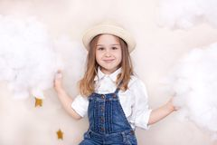 A smiling cute little girl flies in the sky with clouds and stars. Little astrologer Little traveler. The concept of preschool edu. Cation of the child. Close-up royalty free stock image