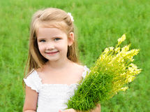 Smiling cute little girl with flowers on the meadow. Adorable smiling little girl with flowers on the meadow in summer day Royalty Free Stock Photo