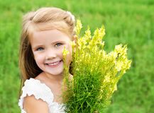 Smiling cute little girl with flowers on the meadow. Adorable smiling little girl with flowers on the meadow in summer day Stock Images