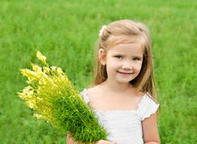 Smiling cute little girl with flowers on the meadow. In summer day Stock Images