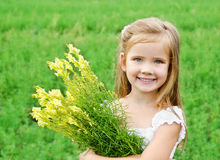 Smiling cute little girl with flowers on the meadow. In summer day Stock Photography