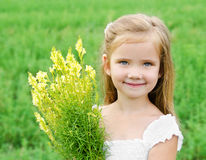 Smiling cute little girl with flowers on the meadow. In summer day Stock Photos