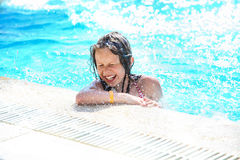 Smiling cute little girl having fun in swimming pool. Pretty little girl swimming in outdoor pool and have fun, smiling Royalty Free Stock Images