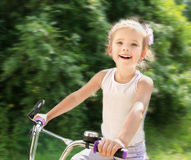 Smiling cute little girl with her bicycle Stock Images