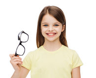 Smiling cute little girl holding black eyeglasses Royalty Free Stock Photo