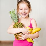 Little girl with a pineapple, banana and lemon Royalty Free Stock Photography