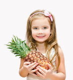 Smiling cute little girl holding ripe whole pineapple Royalty Free Stock Photos