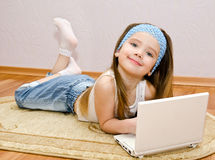 Smiling little girl with a laptop at home on the floor Stock Images