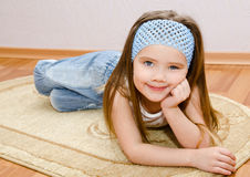 Smiling little girl lies on a house floor Stock Photography