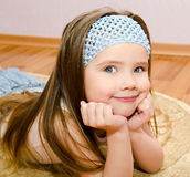 Smiling little girl lies on a house floor Royalty Free Stock Photo