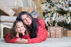Smiling cute little girl with mother near gifts and Christmas tree. New year or Christmas family celebration at home stock photography