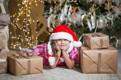 Smiling cute little girl near with santa hat near gifts and Christmas tree. New year or Christmas celebration at home royalty free stock photo
