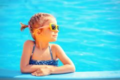Cute girl in pool. Smiling cute little girl in sunglasses in pool in sunny day stock photos