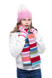 Smiling cute little girl wearing knitted sweater and colorful scarf, hat, mittens isolated on white background. Winter clothes. Stock Images