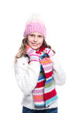 Smiling cute little girl wearing knitted sweater and colorful scarf, hat, mittens isolated on white background. Winter clothes. Royalty Free Stock Image