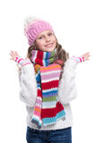 Smiling cute little girl wearing knitted sweater and colorful scarf, hat, mittens isolated on white background. Winter clothes. Royalty Free Stock Photos