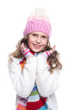 Smiling cute little girl wearing knitted sweater and colorful scarf, hat, mittens isolated on white background. Winter clothes. Royalty Free Stock Images