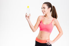 Smiling cute lovely fitness girl looking at bottle of water Stock Photo