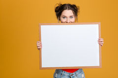 Smiling cute lovely young woman hiding behind blank board. Over yellow background Stock Images