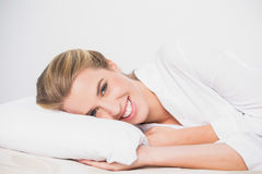 Smiling cute model lying on cosy bed Royalty Free Stock Photography