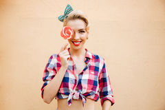 Smiling cute pin up girl covered her eye with lollipop Stock Image