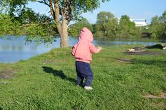 Smiling cute playful little girl is standing on green grass. girl toddler walks around the lake learns to walk. sunny stock images