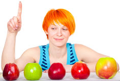 Smiling cute red hair woman choosing apple Stock Images