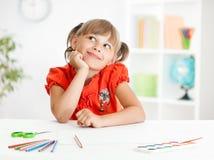 Smiling cute schoolgirl dreaming making homework Royalty Free Stock Photography
