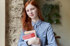 Smiling cute shy young woman with long red hair standing and holding a books Royalty Free Stock Photo