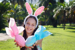 Smiling cute teen girl with rabbit ears holding Easter chocolate. Eggs in colorful paper in park. Selective focus on face Royalty Free Stock Image