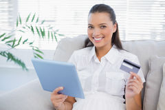 Smiling cute woman buying online using her tablet pc Stock Photos