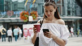 Smiling cute woman with a cup of coffee use mobile phone on crowded city street stock footage
