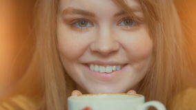 Smiling cute woman holding cup of hot coffee in hands. Inhaling aroma and relaxing