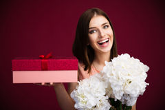 Smiling cute woman holding gift box and flowers Royalty Free Stock Photos