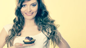 Smiling cute woman holds fruit cake in hand Royalty Free Stock Photos