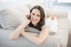 Smiling cute woman lying on a cosy couch having a phone call Royalty Free Stock Image