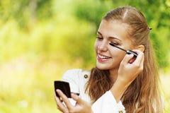 Smiling cute woman paints eyelashes Stock Photography