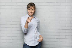 Smiling Cute woman pointing a finger in front of brick wall, loo. Female casual happy studio point fingers gray isolated background Stock Photography