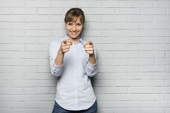 Smiling Cute woman pointing a fingers isolated in front of brick Royalty Free Stock Photography