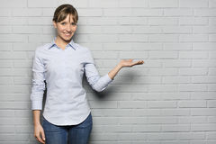 Smiling Cute woman showing empty copy space isolated over a bric Royalty Free Stock Photos
