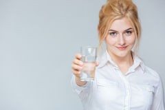 Smiling cute young businesswoman giving you a glass of water Royalty Free Stock Photography