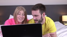 Smiling and cute young couple using laptop in bed at home, online shopping stock video