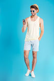 Smiling cute young man standing and using mobile phone. Full length of smiling cute young man standing and using mobile phone over blue background Royalty Free Stock Photography