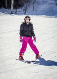 Smiling Cute Young skier skiing downhill. Cute young female skier skiing down a snowy slope on a winter day at a beautiful ski resort in the rocky mountains. She Stock Photo